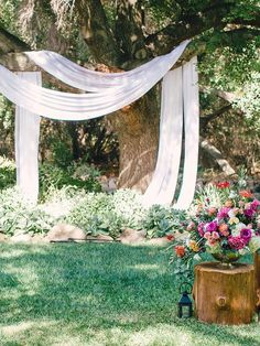 Use the natural surroundings to your advantage on your wedding day by draping loose fabric across tree branches for a DIY rustic ceremony arch idea.