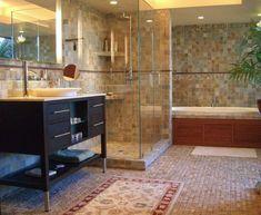 suelos para baños, baño grande con bañera y ducha de obra, paredes con azulejos, espejo grande, ducha de obra con estantes y paredes de vidrio, tapetes y palmera