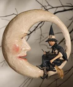 Witch on Moon - Bethany Lowe Vintage Decoration – Black Bow Halloween Shoppe. Hang this beautiful ornament to complete your Halloween vignette! The clear cord gives the impression that the moon and witch are floating high in the sky on All Hallows' Eve. The hand-painted detail of the witch and glittery finish on the moon make this a perfect addition to your vintage collection! Bethany Lowe. Paper mache and resin, with glitter accents. 16″ x 16″. FREE SHIPPING!