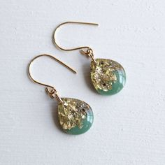 Teardrop earrings are filled with emerald green resin, gold flakes and glitter. They hang from hand formed 14 karat gold filled ear wires with