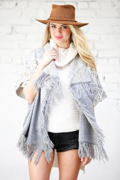 Your winter dreams have come true. Featuring a short sleeve, fringe trim, and knit aztec inspired pattern, this grey cardigan sweater looks perfect over a mock neck top with black denim. Top it off with natural makeup and a suede hat.