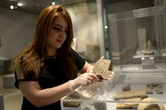 Miss Hazha Jalal, manager of the tablet's section of the Sulaymaniyah Museum, holds the tablet. The Sulaymaniyah Museum, Iraq. Photo © Osama S.M. Amin.