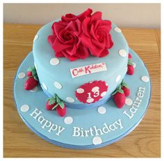 Cath Kidston cake. Strawberry cake filled with vanilla bean buttercream and covered in white chocolate ganache. Finished with polka dots, roses and strawberries.