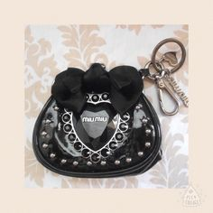 """REDUCED Authentic Miu Miu LTd Edition Coin Purse Limited edition coin purse in black patent leather.  Measures about 4"""" W x 3.5"""" H x .75"""" D.  It has a kiss lock closure, black crystal, silver tone studs and hardware, satin bow and keychain ring.  Gently used with light normal wear.  No trades/no PayPal. Miu Miu Accessories"""