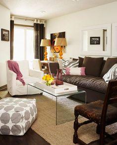 - chocolate brown modern sofa white gray zebra pillows pink lumbar pillow white slipcover chair pink throw acrylic coffee table jute rug white gray pouf orange lamps brown grommet lamps