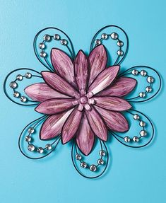 Add visual interest to any room with this beautiful Jeweled Flower Wall Art. This large, 3-D wall sculpture is constructed of shaped metal petals and acrylic gems. The open design lets the background wall color show through. #flower #spring