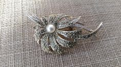 A lovely marcasite flower design vintage brooch with a faux pearl at the centre and pin back fastening. In good vintage conditon, just 2