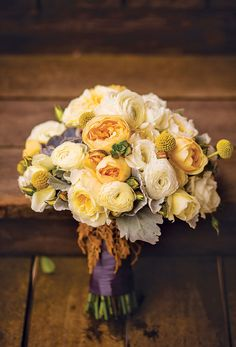 Bouquet of garden roses, ranunculus, billy balls, succulents, and dusty miller