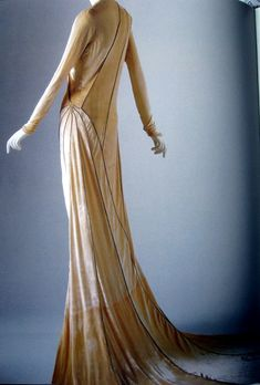 Madeleine Vionnet, 1930s designer, known for 'architectural elements' in her fashions. This gown is cut at an angle, and has panels, and triangular insertions (called godets). This velvet, champagne-colored gown has minimal ornamentation, a simple 'V' neckline, long narrow sleeves & a circular, cathedral train. The weight of the velvet creates a drag on the train, creating a lovely silhouette.