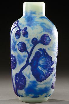 Rare vase à corps ovoïde sur talon plat et col étranglé cylindrique en verre doublé à décor dégagé à l'acide et repris à la roue de fleurs bleues sur fond opaque nuancé bleu à surface martelée. Signature incisée «Daum Nancy». Vers 1900. H : 24 cm