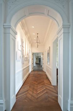 herringbone parquet flooring....amazing. Love the all white plaster work arch & detail. perfect hall way
