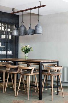 decoracion salon comedor. mesa alta y sillas de madera clara, lámparas colgantes de metal, florero