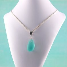 Rare Aqua Beach Glass Necklace. The color of water is so calming,  a symbol of peace and serenity. This beautiful sea glass gem reminds me of carefree days at the beach.  It is also an older piece as it is very thick. The gem measures @ 1″ long by 1/2″ wide. It is expertly wire wrapped to a sterling silver bail and comes with a 16″ sterling silver diamond cut rope necklace from Italy. $89.