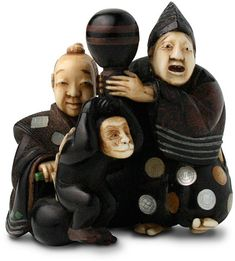 Hirotada wood and ivory netsuke  late 19th century  street performers with monkey  1 5/8 by 1 3/4 in., 4 by 4.5 cm