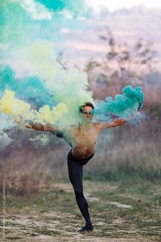 ballet dancer with two smoke bombs dance in nature