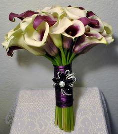 Purple and white calla lily bride bouquet with plum ribbon .