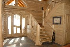 White cedar and glass door entryway along with log paneling and staircase!