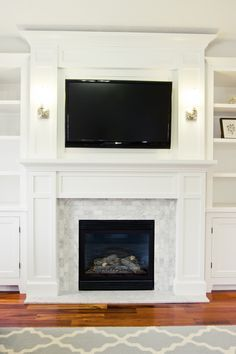 I love the fireplace millwork and the marble subway tile. A painting with blue hues would look lovely above the mantle! PRODUCT SOURCES: The tile is from Lowes. The paint used on the moldings and trim is White Dove by Benjamin Moore. The rug is from rugsusa.com.