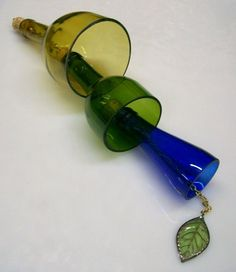 This is a wine bottle windchime. I have been working on this design for a while now and I have just perfected it. It was handmade in my glass studio by me, CDChilds. This windchime would be so beautiful on any porch. It would also be perfect in any home setting to add just a touch of whimsy. Each windchime is a wine bottle that I have cut into a bell shape. I have ground the edges so that they are smooth to the touch. The clapper is a filigree leaf attached to the bottom chain.    The…