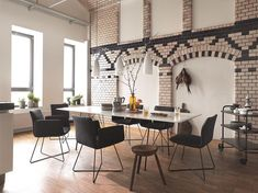 High ceilings, a brick #featurewall, a gorgeous #table, stunning #chairs - this #diningroom designed by Cor Sitzmöbel Helmut Lubke really does have it all. What makes the space extra appealing are the little touches of cosyness like the pot plants on the windowsills, and the #frenchpress coffee plungers. Find more dream spaces with #homify  #house #home #interiordesign #interiordecor #homedesign #homedecor #modernhouse #modernhome #germandesign #europeandesign #madeingermany #rustic…