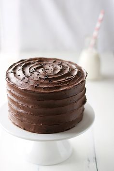 Probably going to heat chocolate frosting to make false fondant icing...on top? Normal, perfect sides with swirl decor