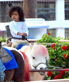 Little rider: North held on tight as her pink-haired pony Marshmallow walked the circuit...