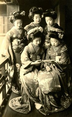 okiya:  Admiring a Folding Fan 1910s (by Blue Ruin1)  Momotaro, seated on the left, and four other Maiko (Apprentice Geisha) admiring the decoration on a folding fan. A vintage postcard from the late 1910s or early 1920s.