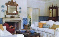 Traditional Portuguese azuelo tiles at chair rail height add a cooling presence, brought out by simple, crisp white linen slipcovers. Michael S. Smith.