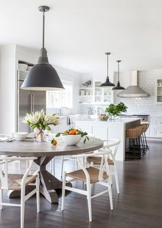 To balance out the glossy all-white kitchen, Simonpietri brought in warm woven barstools from Palecek, a round salvaged-wood dining table from RH, and Wishbone chairs by Hans J. Wegner from Design Within Reach | archdigest.com