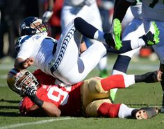Description of . San Francisco 49ers' Ray McDonald (91) sacks Seattle Seahawks' quarterback Russell Wilson (3) in the first half of their fo...