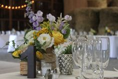 Summer flowers of lavender, yellow and white adorn the settings of these tables.