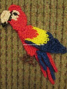 """SCARLET MAKAW made on the Rainbow Loom. Designed and loomed by Jaclyn Lecaros. (Rainbow Loom Obsession FB page) Jaclyn said: """"I have pics of the loom on my wall. I used a double loom for the beak/head, body, and wing. Attached with slip knots. The tail feathers are single rows at different lengths attached with slip knots and the feet also. It took all day to complete, going back and forth with loom and chores..."""""""
