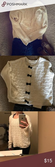 Jessie Simpson cream bow sweater This sweater is cream colored with large knitting, and has the most adorable semi-open back closed with black bows. It fits a little loose and is so comfortable with jeans and flats! Jessica Simpson Sweaters Crew & Scoop Necks