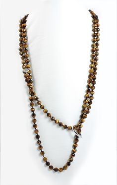 "Tiger Eye Facet Cut 56"" long Necklace with 8mm stone beads knotted in between with orange or black silk thread. Comes with a Sterling Silver Pearl Shorten-er to wear the piece in various different ways. $250"