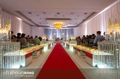 Modern all-white Hindu ceremony with crystals and red carpet aisle via IndianWeddingSite.com