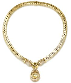 A diamond and sapphire collar necklace, by Cartier, circa 1980  The flattened palmier-link chain, terminating in two brilliant-cut diamond loops, suspending an oval-cut yellow sapphire drop, within a similarly cut diamond surround, diamonds approximately 1.60 carats total, signed Cartier Paris, numbered, French assay mark, necklace length 38.6cm, pendant length 2.9cm, Cartier case