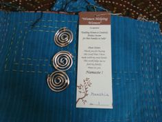 """""""Women Helping Women"""" co-op tag identifying handmade Kantha Scarves  and broaches. made by women in Jaipur, India and being sold in Paris, ON Canada."""