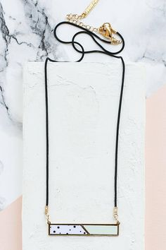 Delicate black necklace with an oblong (horizontal) pendant, comprised of metal and FORMICA®, plated in high-quality silver or 24K gold, according to your choice.  Please select a color combination from the last image.  Measurements: Total length: 45.5 cm / 17.9, + 3.5 cm / 1.4 extension chain. Size of pendant: 0.6*4 cm / 1.5*0.2 If you would like the chain shorter / longer, please message me.  Want to see more necklaces? Click here http://www.etsy.com/shop&...