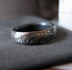 This is a classic domed 6mm wedding band with a comfort fit. Made from .925 sterling silver, it has a rustic hammer marks and a brushed oxidized finish. This is a great wedding band or fashion ring for men who insist on casual jewelry designs.  Comes in a Hot Rox gift pouch and attractive box.  Please allow 5 weeks production time and 3 days shipping for US. If you need this sooner, please contact me as I might be able to create and ship it in as little as 2 days. I offer expedited…