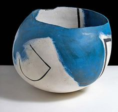 A photo of a wide circular pot painted in white, blue and black