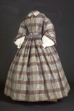 "Brown plaid silk 1850-55 Dress altered; extra scraps saved. Fitted straight waist bodice and skirt gathered to band, originally separate pieces. 1840s bodice had a long pointed cf and long tight fitting sleeves. Now pagoda sleeves worn with white cotton undersleeves. Skirt made of 7 lengths of 23"" w silk taffeta, 160"" at hem, bound in brown cotton. Bodice lined with brown cotton w 2 bones under the gathers, 1 down the rt cf by brass eyes that hook bodice."