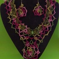 The colors in this necklace are the colors of a vineyard from the greens of the leaves to the maroons and pinks of the grapes. The needle tatted necklace is laced with a 3/8 inch polyester organdy ribbon. Green crystal beads and a medallion complete the center accents.  The necklace, flat, meas...