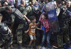 Children cry as migrants waiting on the Greek side of the border break through a cordon of Macedonian special police forces to cross into Macedonia, near the southern city of Gevgelija, The Former Yugoslav Republic of Macedonia. Aug. 21, 2015.