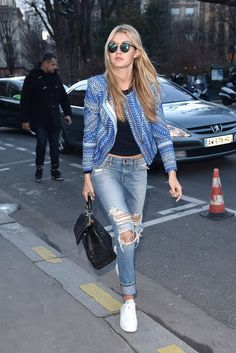 For a casual cool-girl look, Gigi Hadid paired her ripped light-wash denim with white trainers, a black top, and a blue printed jacket.