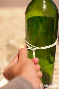How to Cut a Wine Bottle  Gather Up: Cotton String(wrap around bottle up to 6 times)Acetone Nail Polish Remover(soak measured string-place back on bottle)a match(light string on fire until it burns out)pot of ice cold water(place bottle in water right after string burns out)