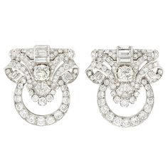 Art Deco Pair of Platinum and Diamond Clips  Topped by pierced scrolled panels supporting tapered circles, centering 2 old European-cut diamonds approximately 3.00 cts., accented by 6 rectangular-cut diamonds approximately 2.00 cts., set throughout with 136 round, 12 baguette and 4 half-moon shaped diamonds approximately 8.75 cts., circa 1935, approximately 22 dwts.
