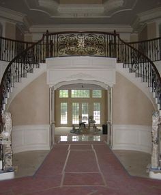 Three Story Foyer Double Curved Staircases with Ornate Iron