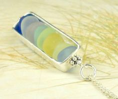 """Brand new design! I began with a genuine sea glass gems from Northern California in shades of all the RAREST colors! I wire-wrapped it in Sterling Silver and suspended it inside of this Sterling Silver rectangular cage. A new modern twist to sea glass! Hours of love went into creating this piece !! The pendant measures 1/3"""" by 1 1/2"""". An 18 inch Sterling Silver chain is included. Like all my jewelry, this necklace comes beautifully-boxed with pretty ribbon -ready for g..."""