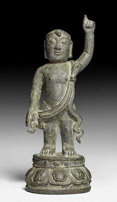 A BRONZE FIGURE OF BUDDHA AS A CHILD. China, Ming dynasty, height 19 cm. Remains of gold lacquer. Bronze mit Verkrustungen, dunkler Patina und Resten von Lackvergoldung. Buddha wird als kleines Kind dargestellt, das auf einem runden Lotossockel steht und dessen Nacktheit mit einer geschwungenen Schärpe verhüllt wird. Buddha verkündet unmittelbar nach seiner Geburt seine allgegenwärtige Verehrungswürdigkeit und weist mit einem Zeigefinger in den Himmel und mit dem anderen zur Erde.
