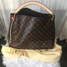 This Authentic Louis Vuitton Artsey MM was made in France and has never been used. It comes with its original receipt . It features 1 rounded leather handle. Brand: Louis Vuitton label was founded by                                                                                                                                                                                  More